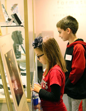 children inspecting exhibit case